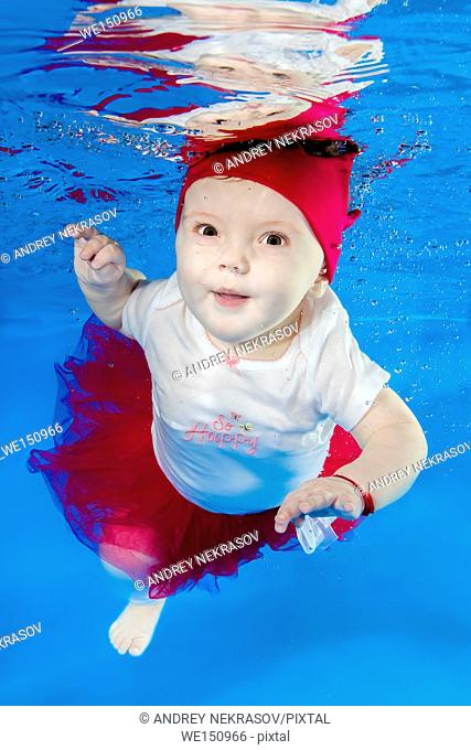 Litle girl in red dress and crown posing under water in swimming pool, Odessa, Ukraine