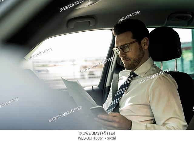 Successful businessman sitting in car reading files