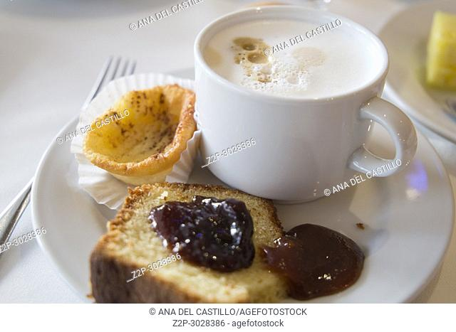 Portuguese breakfast: nata pastry, sponge cake with jam and coffee
