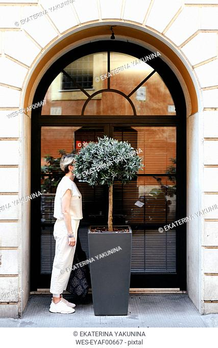 Woman hiding her head in a big potted plant in the city, Rome, Italy