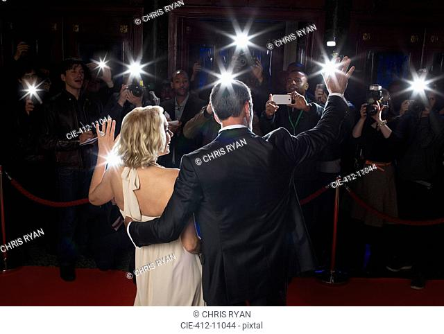 Rear view of well dressed couple waving to paparazzi at red carpet event