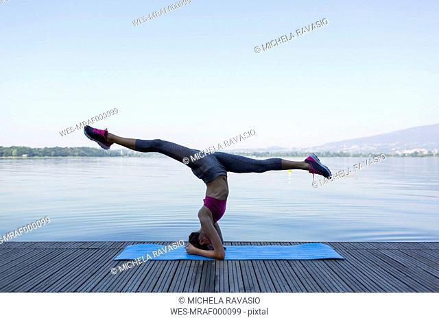 Young woman doing exercise on pier, headstand