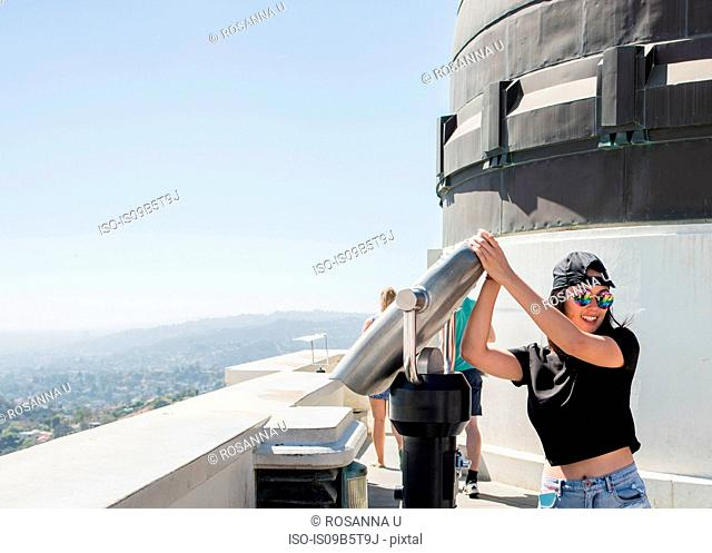Young woman fooling around with coin binoculars at Griffith Observatory, Los Angeles, California, USA
