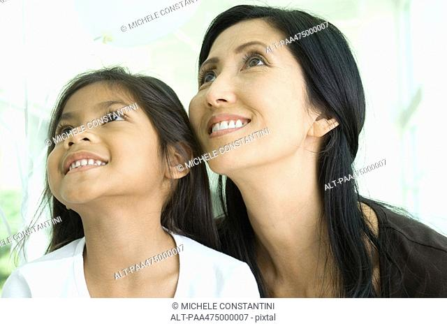 Mother and daughter looking up and smiling together, close-up
