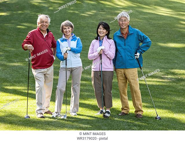 Two young senior golfing couples on the course and ready to play