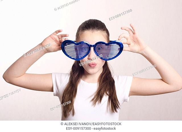 Teen girl in a great mood wore big glasses in the shape of heart