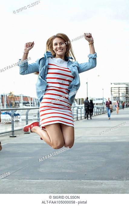 Young woman jumping for joy outdoors