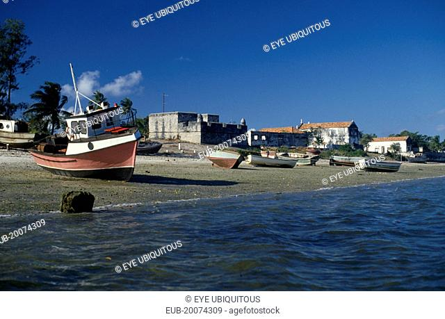 Fishing boats pulled up on shore with crenellated walls of fort behind