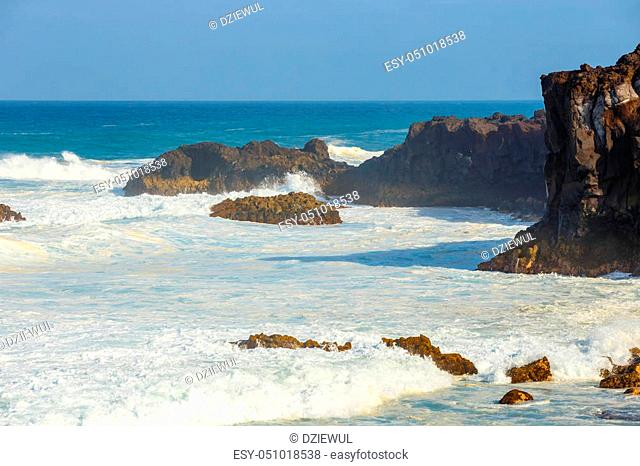 Los Hervideros, volcanic coastline with wavy ocean and blue sky, Lanzarote island, Spain