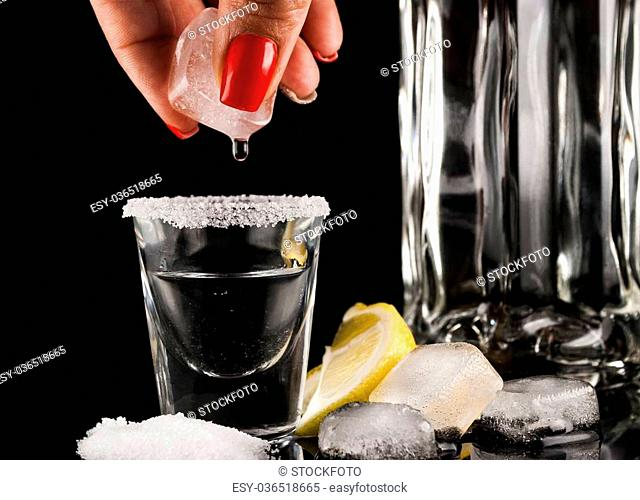 Tequila with lemon or lime and salt on reflex background