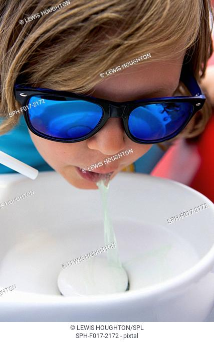 MODEL RELEASED. Young boy wearing protective goggles using mouth wash in sink at dentists surgery