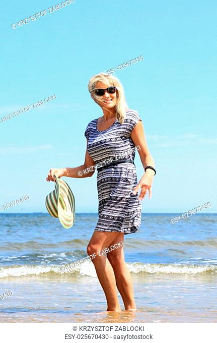mature woman with a hat on beach enjoying summer holiday
