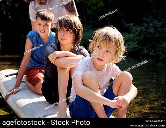 Thoughtful boys sitting on paddleboard in stream at forest