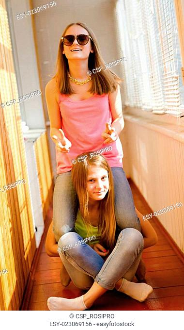 Two funny happy teenage girls having fun riding on back