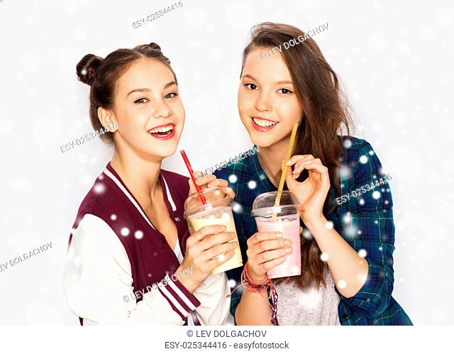 winter, christmas, people, teens and friendship concept - happy smiling pretty teenage girls or friends drinking milk shakes and with straw over gray background...
