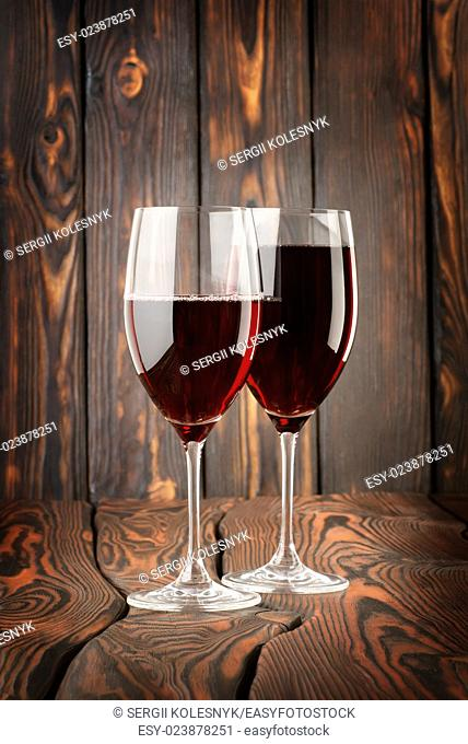 Two glass of red wine on a wooden background