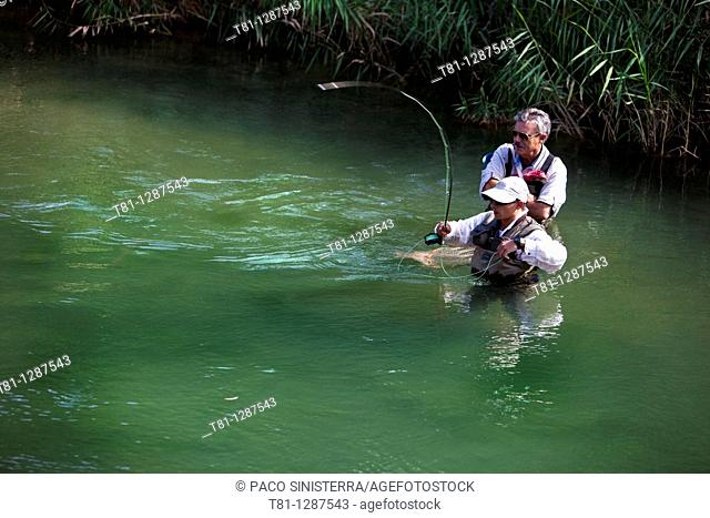 Father and son fishing in the river