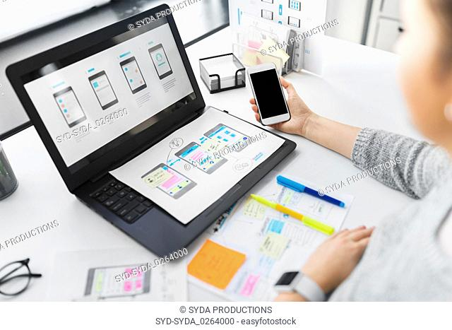 web designer with smartphone and laptop at office