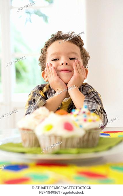 Four year old boy waiting for a cupcake