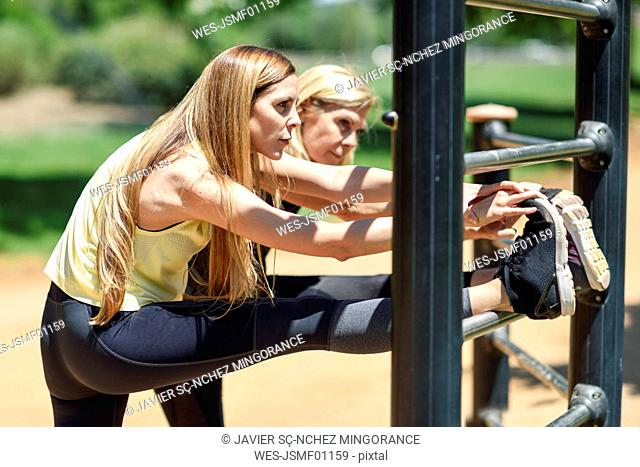 Mature woman exercising with her daughter in a park