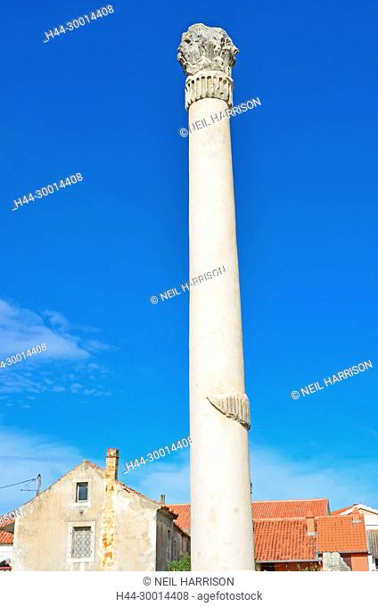 A reconstructed tall roman column with a corinthian capital from a ruined temple in the middle of a town