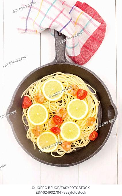 spaghetti with grilled prawns, tomato and lemon slice in a cast iron pan