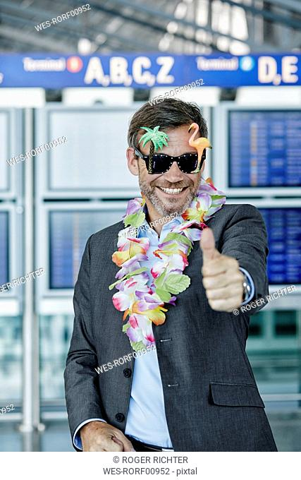 Smiling businessman dressed up as tourist at the airport