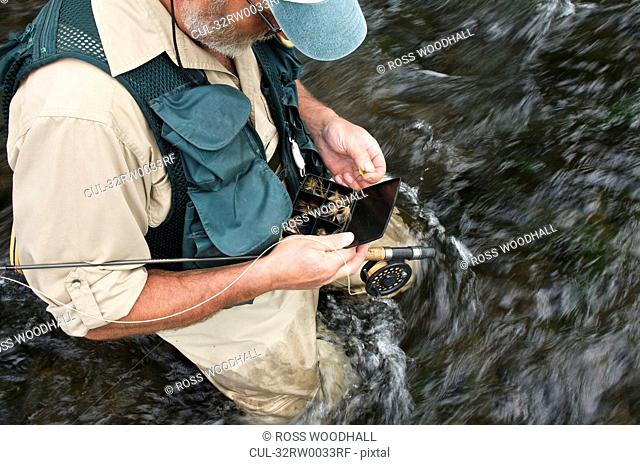 Fly fisherman holding fly box in river