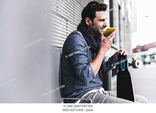 Businessman with skateboard sitting at bus stop using smartphone