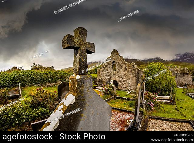 Dark stormy sky over an old graveyard and ruins of a stone cchurch