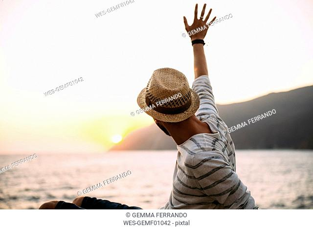 Greece, Cylcades Islands, Amorgos, man waving and enjoying the sunset next to the sea