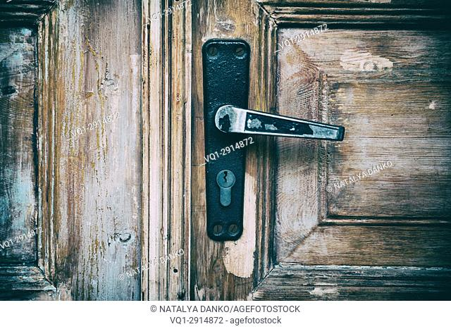 Entrance brown wooden door with an iron lock and an iron handle