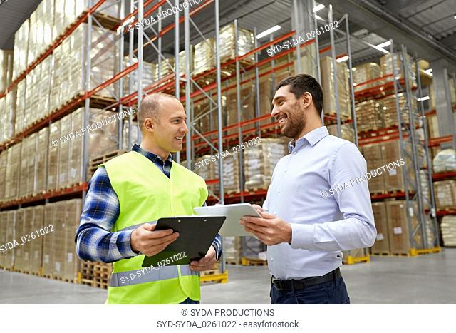 worker and businessman with tablet pc at warehouse