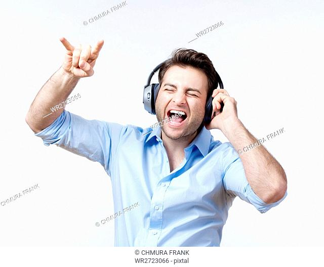 adult, audio, beat, blue, Caucasian, earphones, enjoy, entertainment, excited, expression, face, fun, guy, happy, headphone, headphones, hear, isolated, leisure