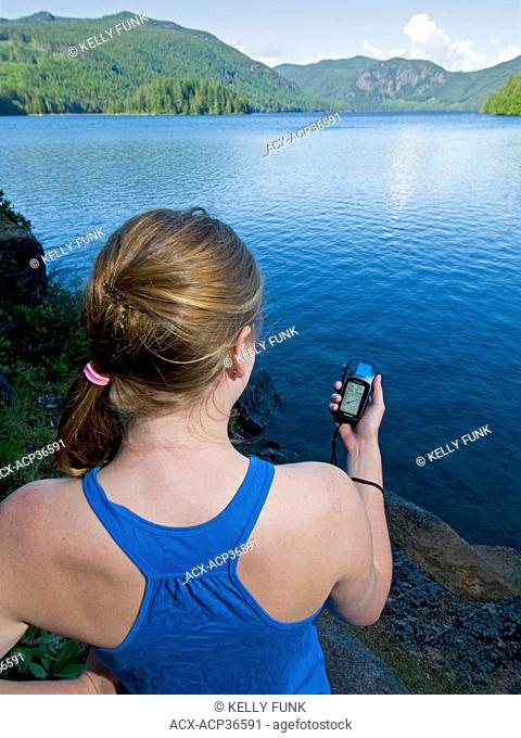 A young woman geocaches where you use a GPS to hide and seek containers with other participants in the activity on the famous 'Forest canoe route' near Powell...