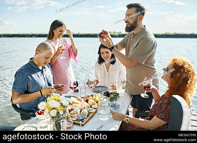 Friends having dinner at a lake taking smartphone picture