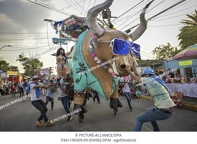 08 March 2019, Mexico, Tultepec: A papier-mché bull filled with fireworks is towed through a street. Around the 8th of March, in Tultepec