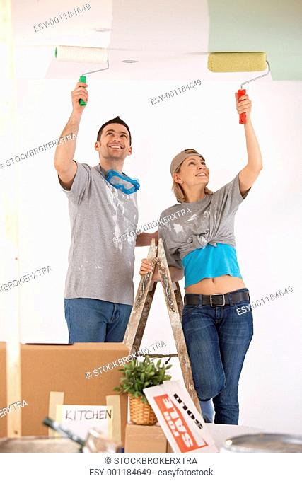 Smiling couple painting ceiling