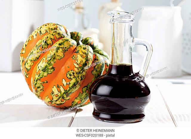 Multicoloured squash (Cucurbita maxima) and carafe with pumpkin seed oil, studio shot