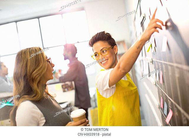 Creative businesswomen planning, scheduling at calendar blackboard