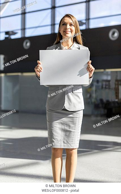 Woman holding blank paper at the airport