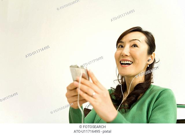 A Mature Adult Woman Listening to Music with a Portable Music Player, Low Angle View, Copy Space