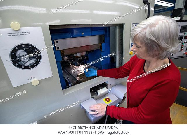 Minter Carmen Lahr takes a newly minted 2-Euro-coin with the portrait of the former German Chancellor Helmut Schmidt out of the embossing machine in the mint...