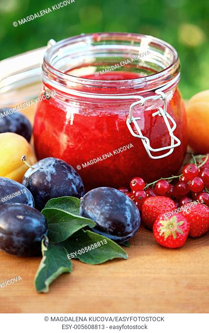 Jar with fresh jam and fruits in the garden