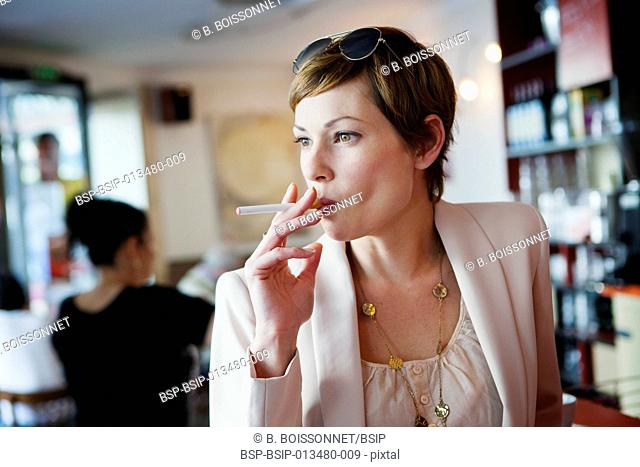 ELECTRONIC CIGARETTE Woman with an electronic cigarette in a public place