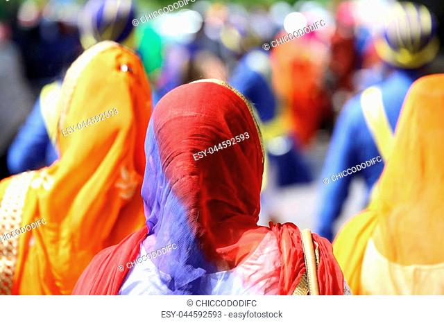 Sikh women with veils over their heads during the procession through the streets of the city