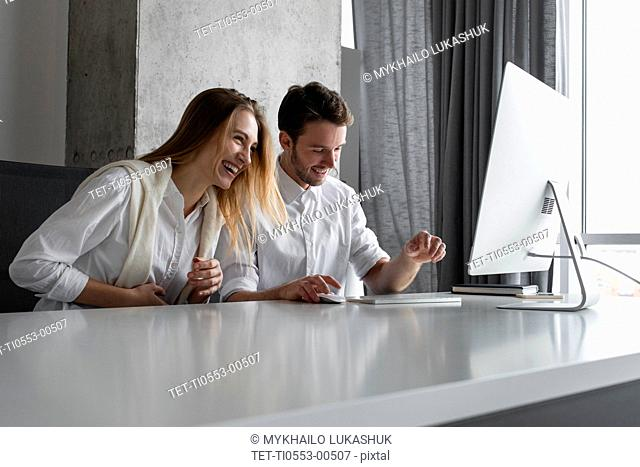 Colleagues laughing at desk