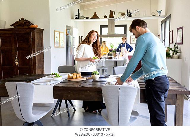 Two couples cooking and laying table together