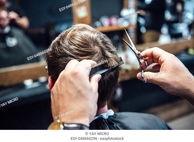 the master in the barbershop shaves and cuts the man in front of the mirror