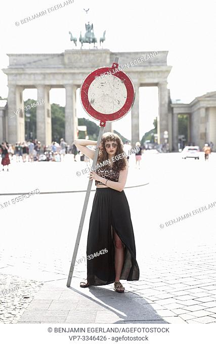 young woman holding No thoroughfare sign in front of national landmark Brandenburg Gate, Brandenburger Tor, in Berlin, Germany